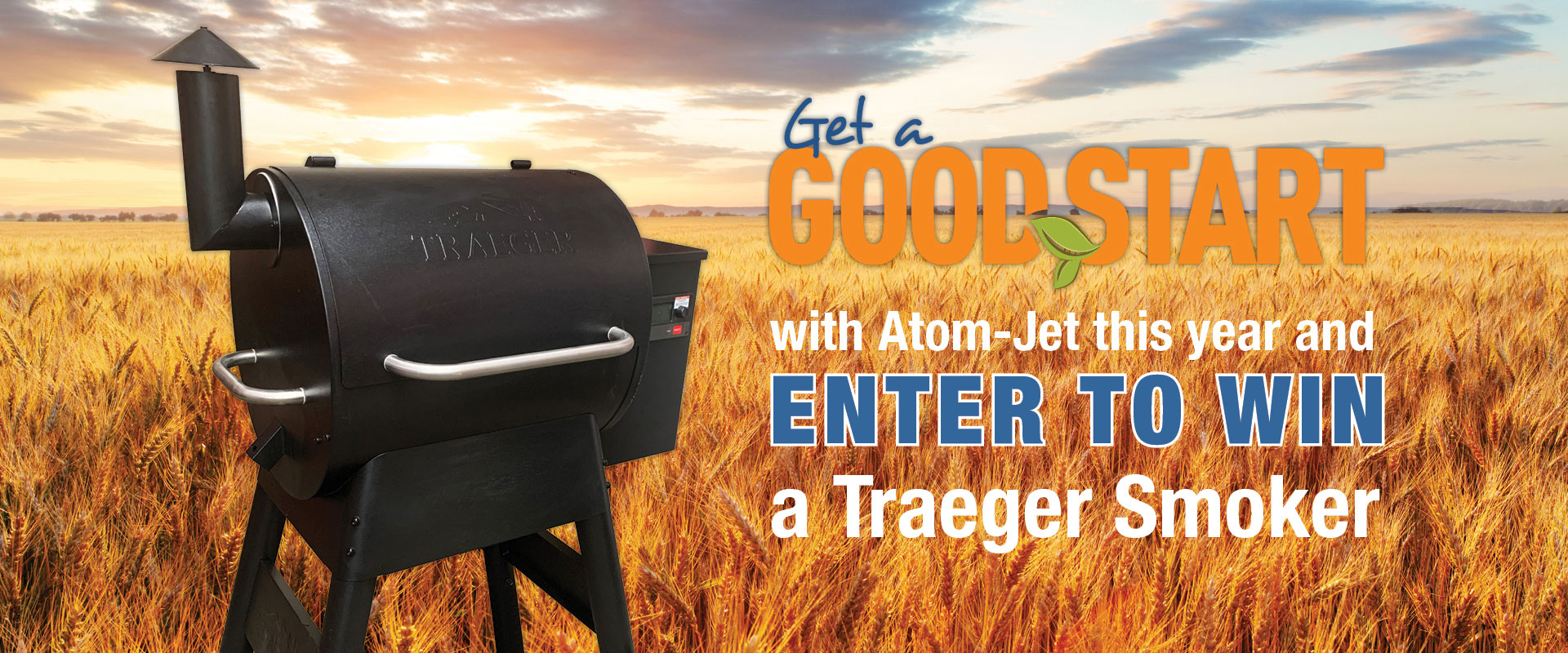 Traeger smoker against a field of grain ready for harvest: Get a Good Start with Atom-Jet this year and Enter to Win a Traeger Smoker!
