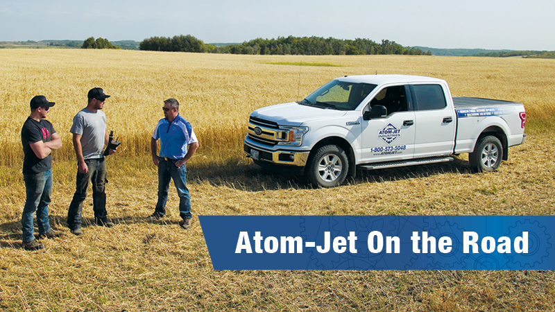 Atom-Jet territory manager in the field during harvest, speaking with two client farmers.